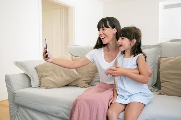 幸せな興奮のお母さんと小さな娘が自宅のソファーに一緒に座っている間、ビデオ通話に電話を使用して