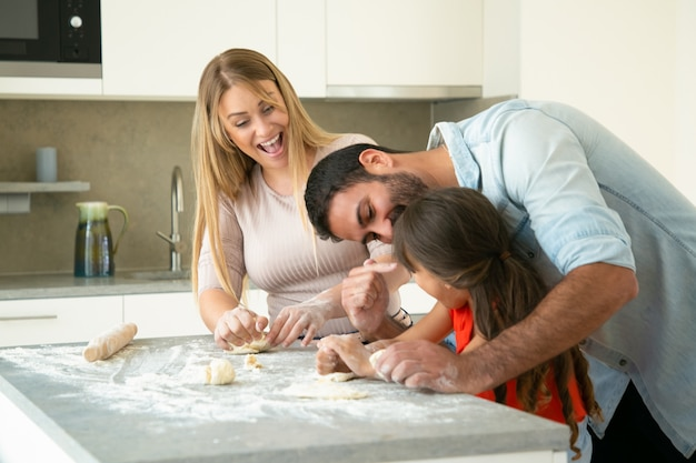 Happy excited mom and dad having fun while teaching daughter to make dough at kitchen table. young couple and their girl baking buns or pies together. family cooking concept