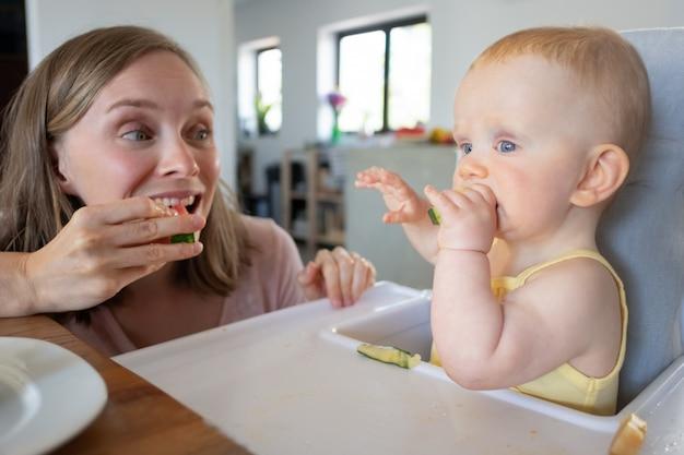 娘と一緒にスイカを食べて、固形食を噛む幸せな興奮しているママのトレーニング赤ちゃん。クローズアップショット。育児や栄養の概念