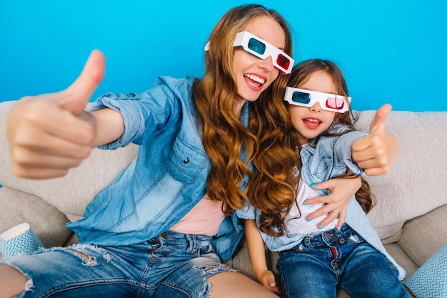 Happy excited mother hugging little cute pretty daughter on couch on blue background. watching 3d movie in glasses together, wearing jeans clothes, expressing positivity and happiness to camera