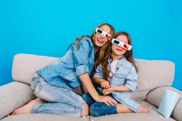 Happy excited mother with cute pretty daughter on couch on blue background. watching 3d movie in glasses together, wearing jeans clothes, expressing positivity and happiness to camera
