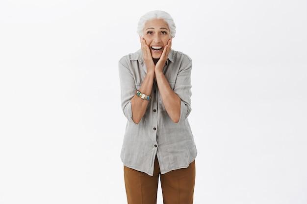 Signora anziana eccitata felice che sorride sorpresa e che osserva
