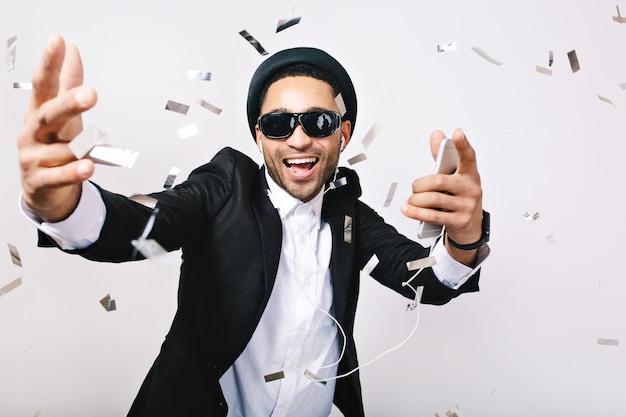 帽子、スーツ、ティンセルで楽しんでいる黒いサングラスでうれしそうなハンサムな男の幸せな興奮したパーティータイム。ヘッドフォン、祝う、歌手、スーパースターで音楽を聴く。