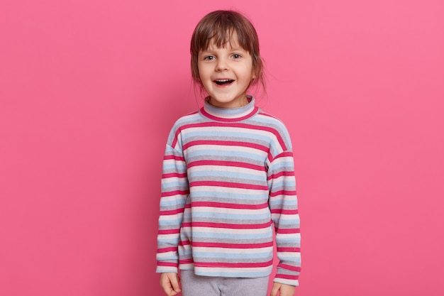 Happy excited preschooler girl wearing casual style striped shirt posing isolated over pink wall