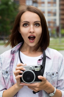 Счастливая excited милая девушка в розовой футболке держа винтажную камеру внешний.