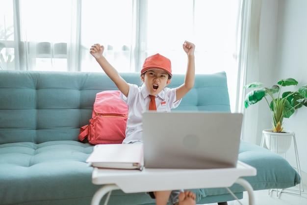 制服を着た幸せな興奮した小学生が自宅でのオンライン授業中に腕を上げる