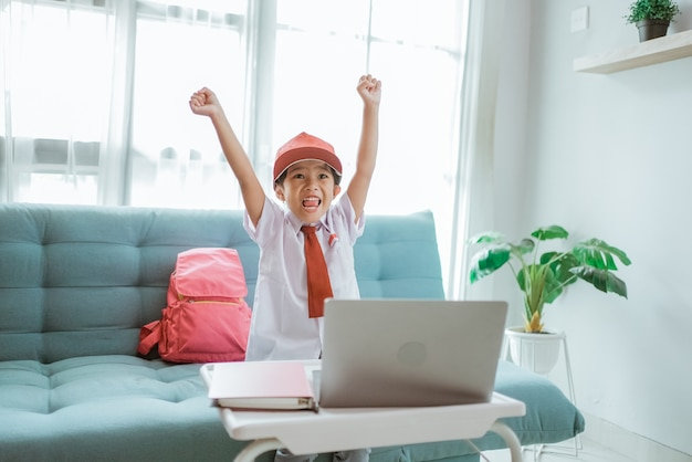 Happy excited primary school student with uniform raise her arm during online class at home