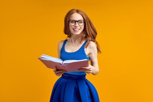 행복 한 흥분된 빨간 머리 여자 책을 읽고 오렌지 배경 스튜디오 초상화 교육 개념에 고립 된 파란 드레스를 입고 완벽 한 함박 웃음으로 카메라를 찾고 점프