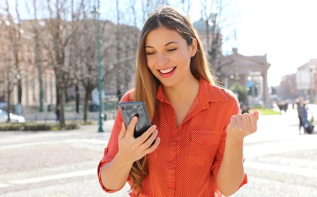 スマートフォンを屋外で読んで、街で祝う幸せな興奮して満足している女性