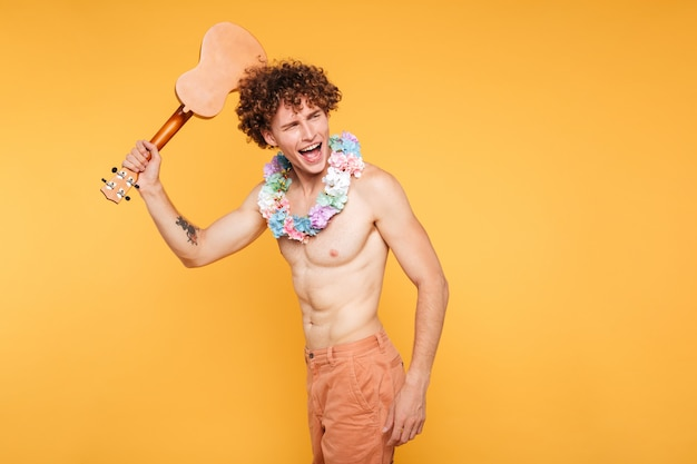 Happy excited shirtless man holding ukulele and looking away