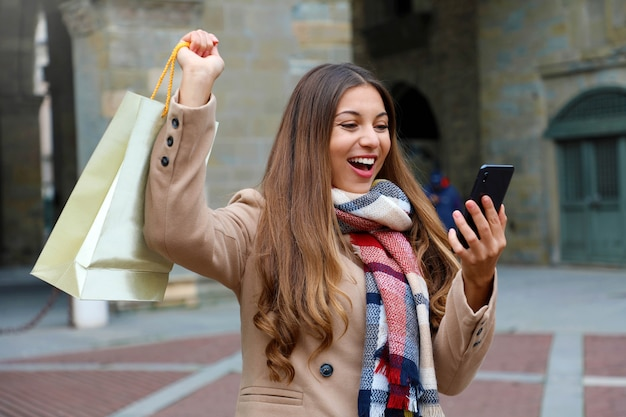 Happy excited shopper woman laughs watching phone raised arm with shopping bag outdoor in city street
