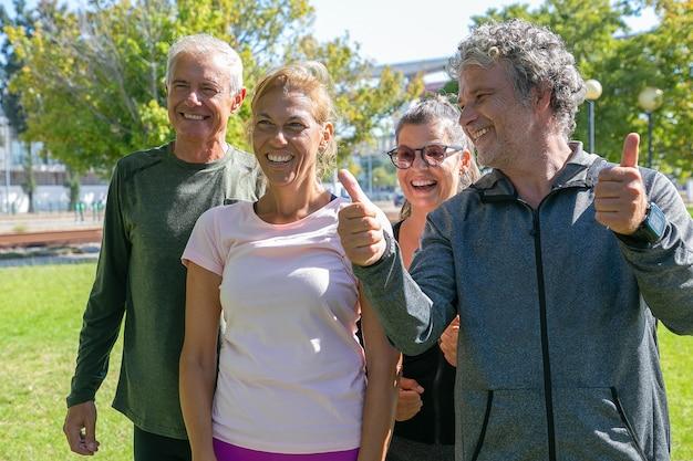 公園での朝の運動の後に一緒に立って、目をそらして笑って、親指を立てるジェスチャーをしている幸せな興奮したスポーティな成熟した人々。退職またはアクティブなライフスタイルの概念