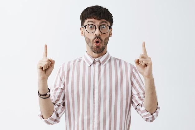 Ragazzo barbuto elegante felice ed emozionato in posa contro il muro bianco con gli occhiali