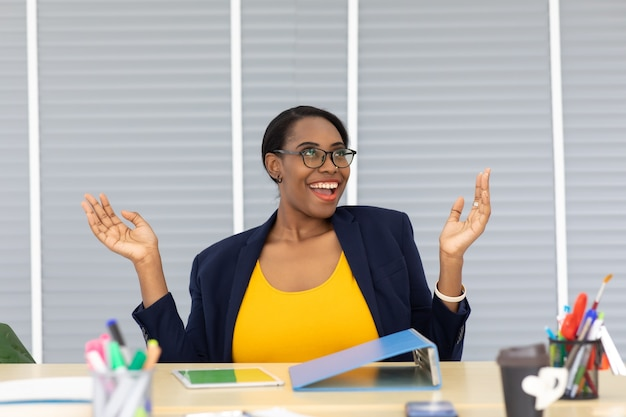 Счастливый возбужденный успешный красивая афро-американская коммерсантка, торжествуя в современном офисе с компьтер-книжкой, успех счастливой позе. работа из дома