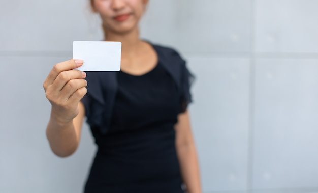 Happy excited successful beautiful businesswoman holding credit card mock up on hand.