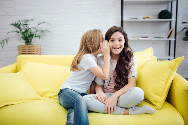 Happy and excited teenagers sit on sofa in room. first girl whisper into ear of her friend. brunette teenager smile.