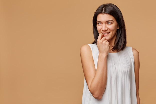 Happy excited thinking of something pleasant tanned woman standing holding a finger in her mouth, with warm smile looks to the left side of the empty space,