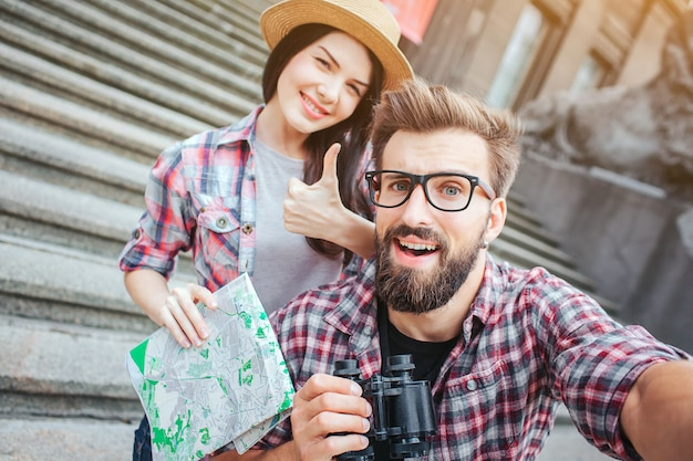 Happy and excited tourists stand on stairs and pose on camera. bearded young man holds it. she shows big thumb up and keeps map in hand.