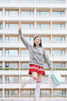 片足で立って腕を空中に上げる紙袋を持つ幸せな興奮したベトナムの10代の少女