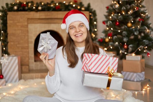 행복 한 흥분된 여자 산타 클로스 모자와 손에 선물 상자 흰색 스웨터에 카메라를 직접보고, 크리스마스 선물을 얻을 행복 되 고, 크리스마스 트리 근처 카펫에 바닥에 앉아.