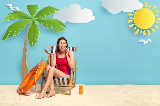 Felice donna eccitata in costume da bagno rosso, si rilassa sulla sedia a sdraio al litorale di mare spiaggia sabbiosa, parla sul cellulare