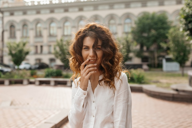 Felice donna eccitata con riccioli che toccano le sue labbra e in posa su vecchi edifici della città