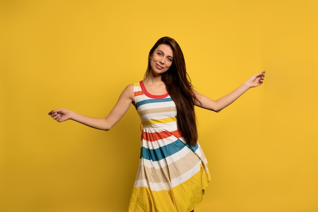 Happy excited woman with long dark hair in bright striped summer dress has fun and dancing happy emotions of european woman .