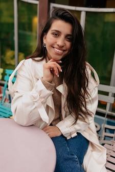 オープンスペースのカフェテリアに座ってコーヒーを待っているベージュのコートを着て長い黒髪の幸せな興奮した女性