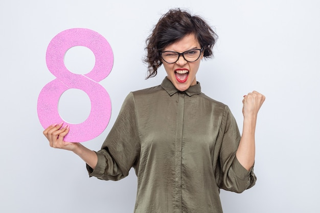 Happy and excited woman with short hair holding number eight made from cardboard looking at camera clenching fist celebrating international women's day march 8 standing over white background