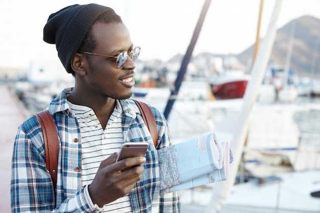 Happy excited you afro american male backpacker in stylish sunglasses and hat holding paper map under his arm, using online navigation app on cell phone before his journey