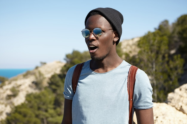 Happy excited young african american male traveler in stylish shades and headwear looking stunned, keeping mouth wide opened while standing high in mountains and admiring beautiful view below