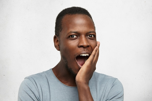 Happy excited young afro-american man in grey t-shirt opening mouth in amazement, touching his face and gazing with fascinated expression, stunned with great idea that crossed his mind