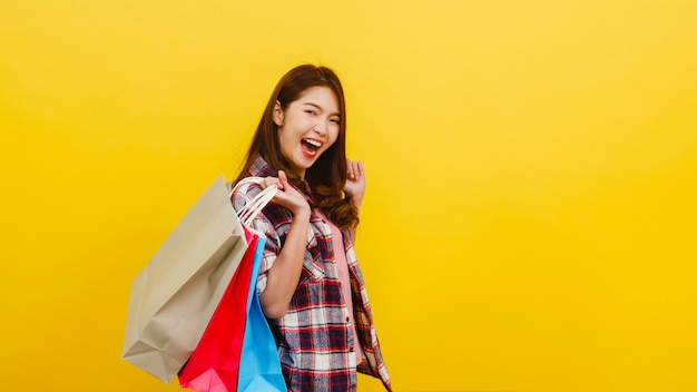 Happy excited young asian lady carrying shopping bags with hand raising up in casual clothing and looking at camera over yellow wall. facial expression, seasonal sale and consumerism concept.