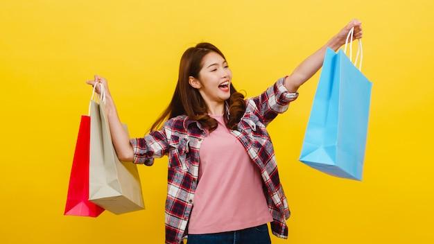 Sacchetti della spesa di trasporto della giovane signora asiatica emozionante felice con la mano che si alza su in abbigliamento casual e che esamina macchina fotografica sopra la parete gialla. espressione facciale, vendita stagionale e concetto di consumismo.