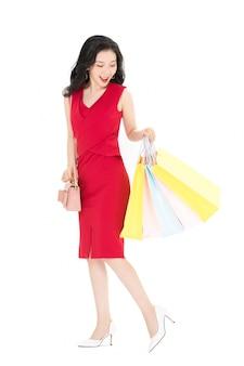 Счастливая возбужденная молодая азиатская дама, несущая хозяйственные сумки с рукой, поднимающей вверх
