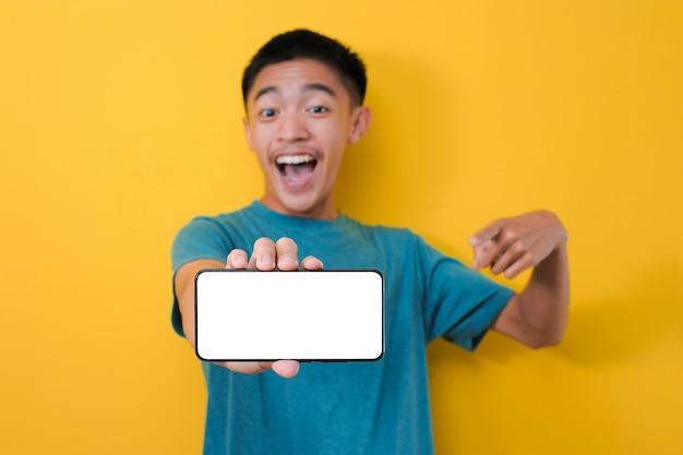 幸せな興奮した若いアジア人男性のショックは、コピースペースの空白の電話画面を指し、黄色の背景で隔離のカメラで白い電話画面を表示します
