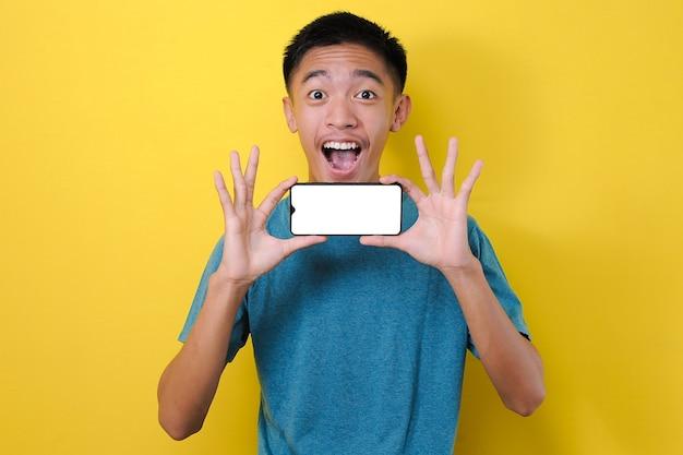 黄色の背景で隔離のカメラで白い電話画面を示す幸せな興奮した若いアジア人男性ショック