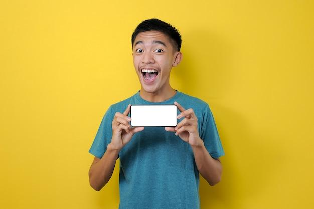 黄色の背景で隔離のカメラで白い電話画面を示す幸せな興奮した若いアジア人男性