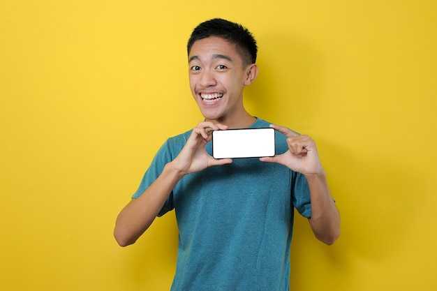 Happy excited young asian man showing white phone screen at camera, isolated on yellow background