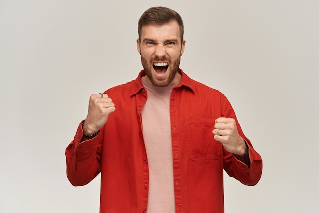 Happy excited young bearded man in red shirt shouting and celebrating victory over white wall looking at front