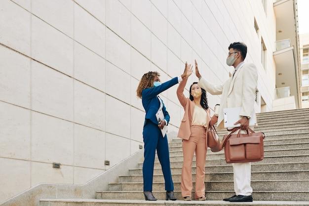 Счастливые взволнованные молодые деловые люди стоят на ступенях и дают друг другу пять, чтобы отпраздновать успешное завершение проекта