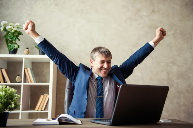 Happy excited young businessman sitting on workplace and celebrating success