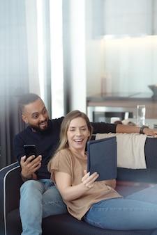 Digitaタブレットでショーの驚くべき最終エピソードを見ている幸せな興奮した若いカップル