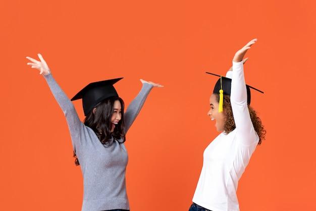 Счастливые взволнованные молодые студентки, носящие выпускные кепки, улыбающиеся руками, поднимающими празднование дня выпуска, изолированы на оранжевой стене