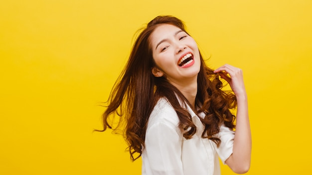 Happy excited young funny asian lady listening to music and dancing in casual clothing over yellow wall. human emotions, facial expression, studio portrait, lifestyle concept.