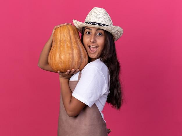 Felice ed eccitata giovane ragazza giardiniere in grembiule e cappello estivo tenendo la zucca sorridente allegramente in piedi sopra la parete rosa