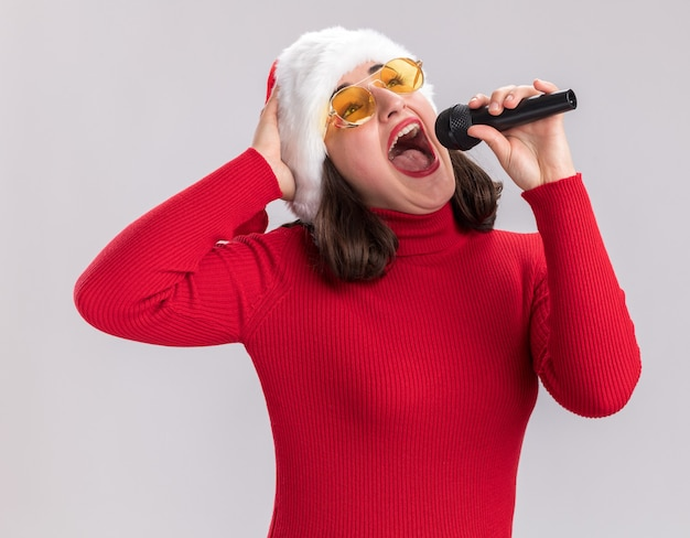 Ragazza felice ed eccitata in maglione rosso e cappello da babbo natale con gli occhiali in possesso di microfono che canta una canzone in piedi sul muro bianco