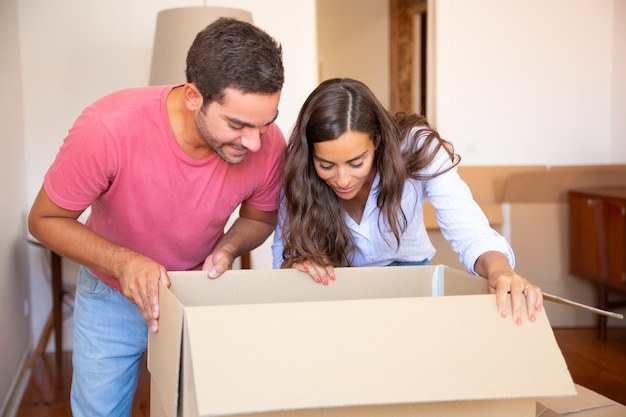 Giovani coppie latine eccitate felici che aprono la scatola di cartone e che guardano dentro, spostano e disimballano le cose