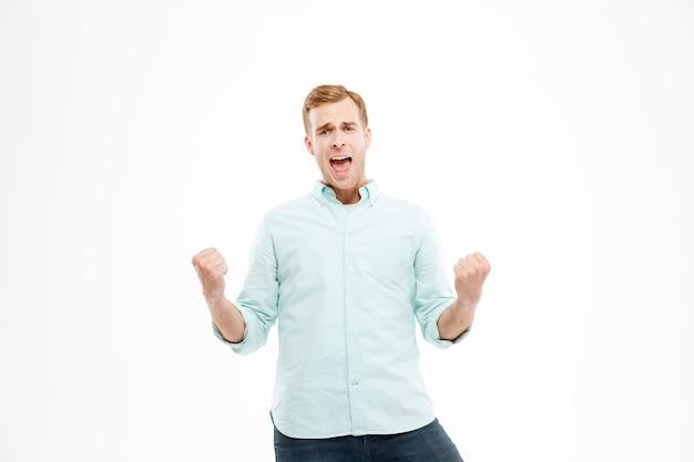 立って、白い壁の上の成功を祝う幸せな興奮した若い男