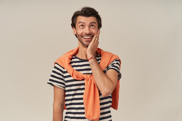 Happy excited young man with stubble in striped tshirt and sweater on shoulders keeps hand on cheek and looking up to the sky